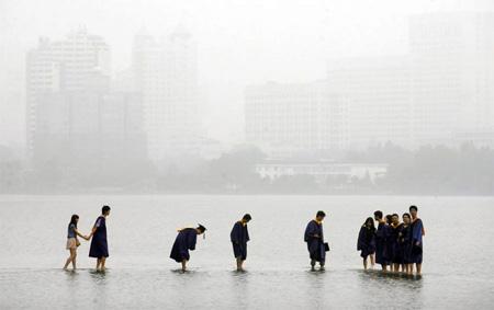 Китайские выпускники стоят в мантиях на затопленном мосту в Ухане